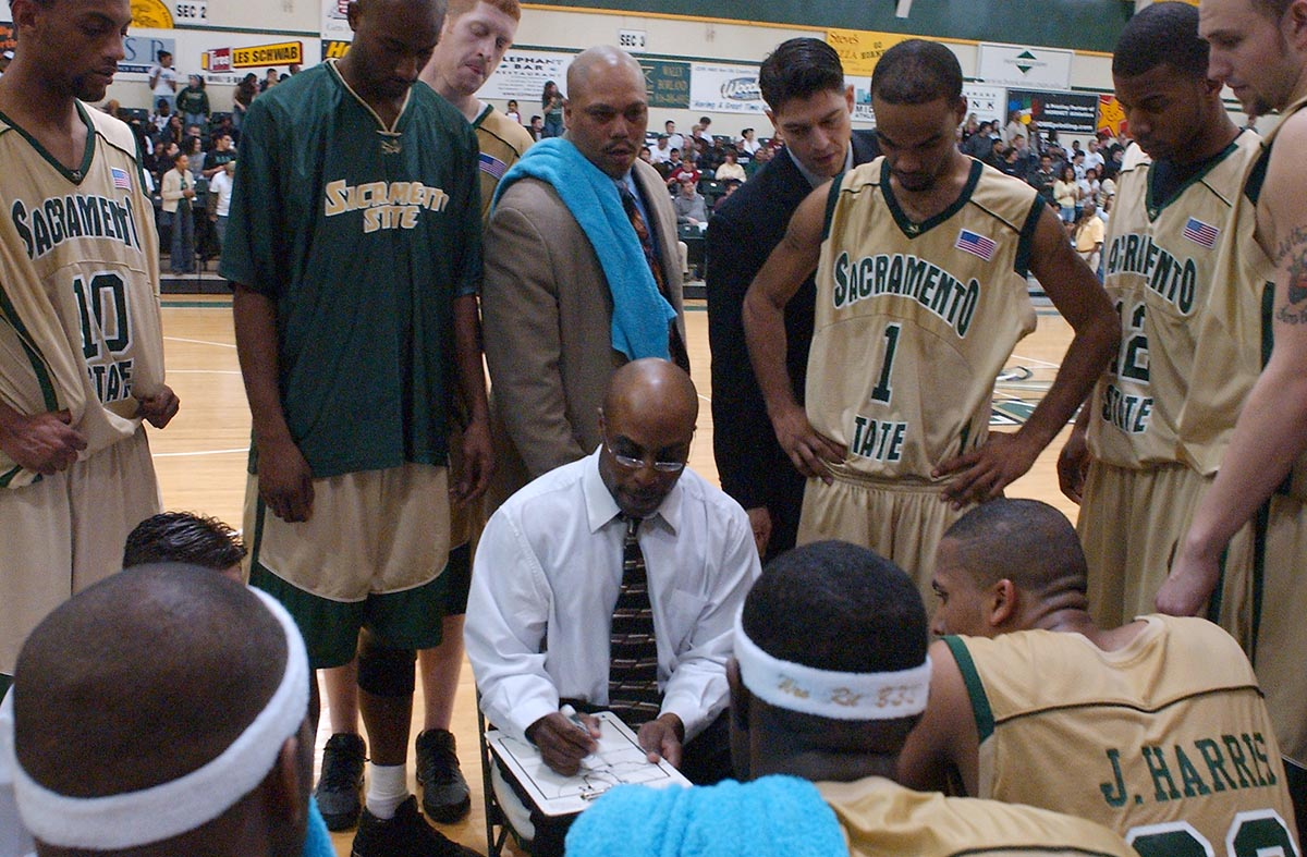 image of Jenkins leading sideline huddle during a Sacramento State game.